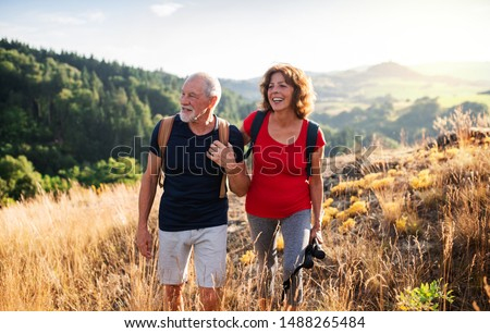 Senior tourist couple travellers hiking in nature, walking and talking.