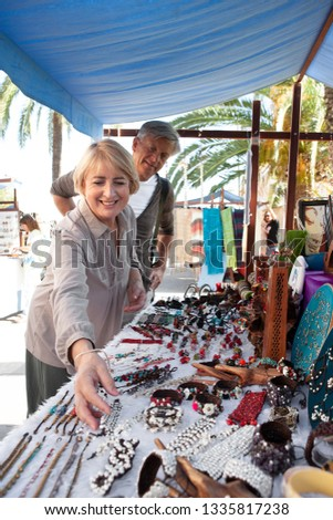 Senior tourist couple visiting artisan market on holiday city break, shopping souverins outdoors, smiling. Consumer mature mand and woman retirement activities, travel recreation leisure lifestyle. #1335817238