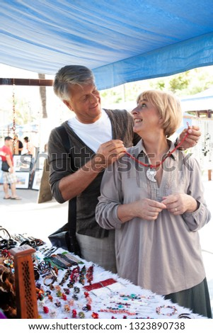 Senior tourist couple visiting artisan market on holiday, shopping souverins outdoors, smiling. Consumer mature people buying gifts, retirement activities, travel recreation leisure lifestyle.