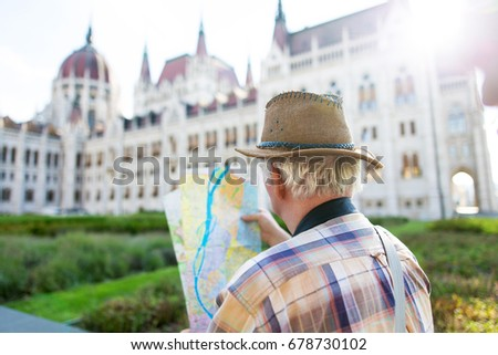 Senior tourist man in hat watching map at Parliament, Budapest, Hungary