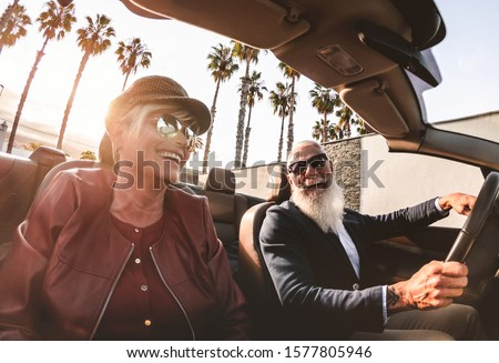 Senior trendy couple inside a convertible car on holiday time - Mature rich people having fun doing a road trip during vacation - Travel, fashion and joyful elderly concept - Main focus on man face
