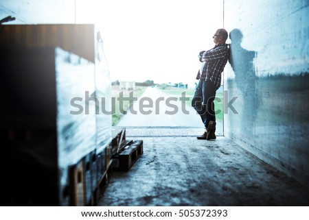 Senior truck driver standing with crossed arms.