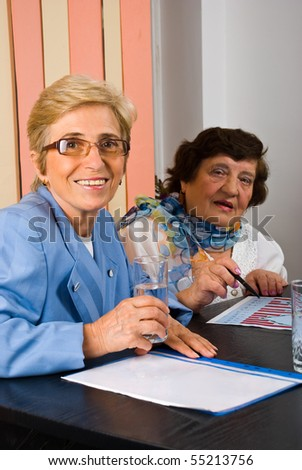 Senior two business women having meeting and looking at camera smiling