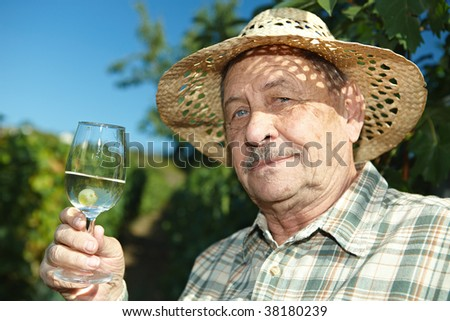 Senior vintner tasting wine outdoors in vinery.