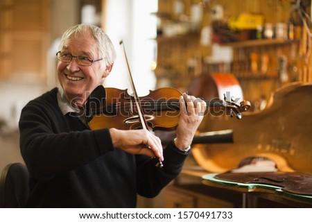 Senior violin maker testing violin