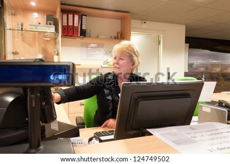 Senior volunteer female cashier at work at the museum front desk