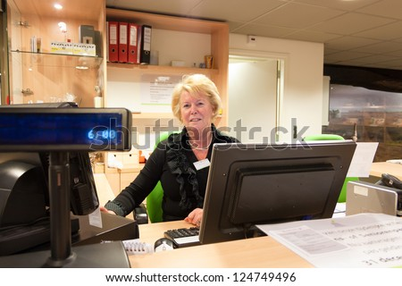 Senior volunteer female cashier at work sitting at the museum front desk