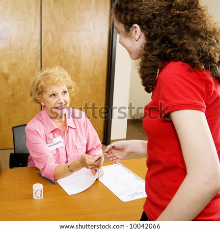Senior volunteer handing out I VOTED stickers at the polling place. - stock photo