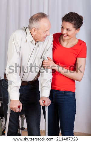 Senior walking with crutches insured by physiotherapist