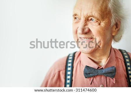 Senior well-dressed man looking aside