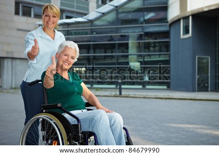 Senior wheelchair driver and nurse holding thumbs up