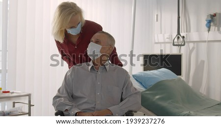 Senior wife in protective mask pushing discharged male patient on wheelchair in hospital. Aged male patient wearing safety mask sitting in wheelchair while wife taking him home from clinic Сток-фото ©