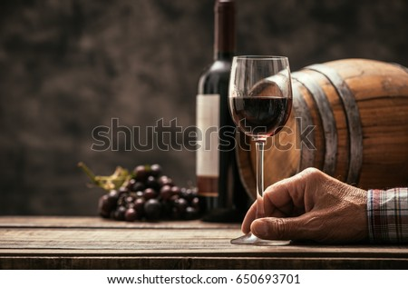 Senior wine maker tasting a glass of red wine in his cellar, wine bottle and wooden barrel on the background, wine tradition and culture concept