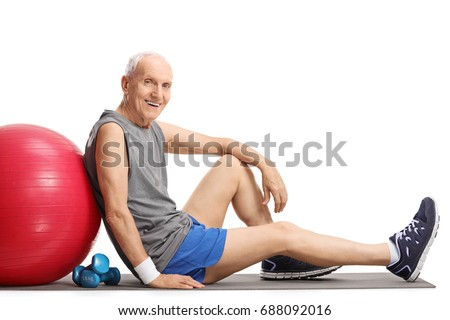 Senior with a pilates ball and dumbbells sitting on an exercise mat isolated on white background