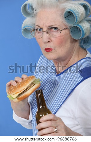 senior with curlers in her hair drinking beer and eating hamburger