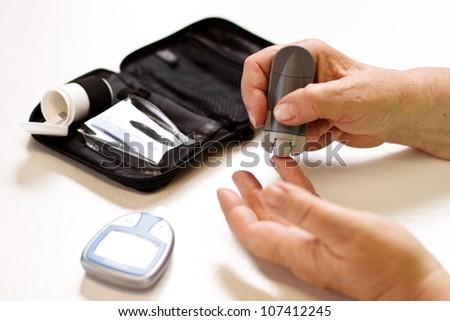 senior with equipment of blood sugar test
