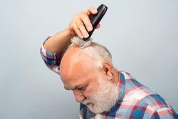 Senior with hair clipper. Old bald man hair clipper, Mature baldness and hair loss concept.