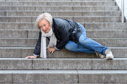Senior woman accidentaly falling down stone steps outdoors