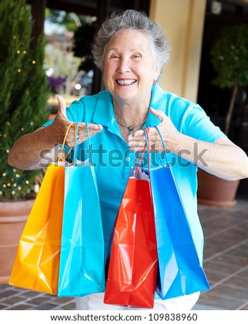 Senior woman addicted to shopping, holding up a handful of bags. - stock photo