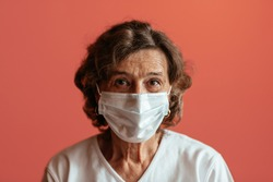 Senior woman against pink background looking straight at camera wearing face mask. Head and shoulders of old woman wearing protection mask.