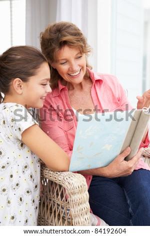 Senior woman and granddaughter with photo album