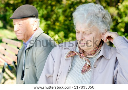 Senior woman and her husband looking away after an argument