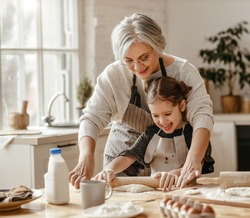 Senior woman and little girl  while rolling soft dough during pastry preparation in cozy kitchen at home