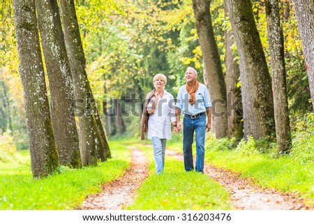 Senior woman and man, a couple, embracing each other having walk in the fall forest #316203476