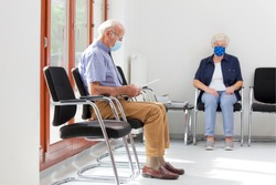 Senior woman and man sitting with face masks in a bright waiting room of  a hospital or an office