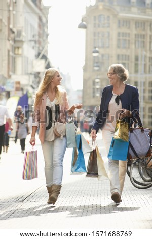 Senior woman and teenage granddaughter shopping in city