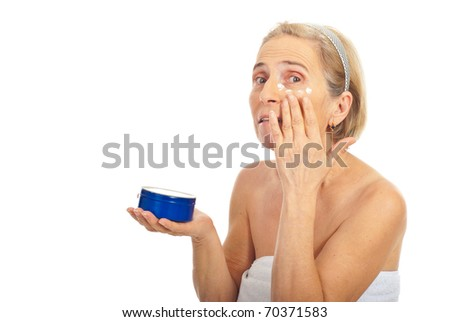 Senior woman applying cosmetic cream around eye and looking camera isolated on white background