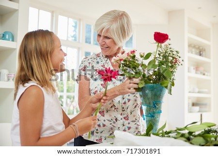 Senior woman arranging flowers with granddaughter at home