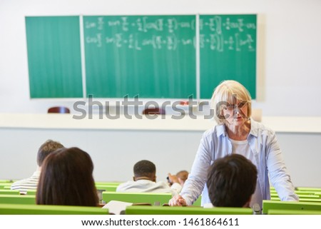 Senior woman as university lecturer teach students in lecture hall #1461864611
