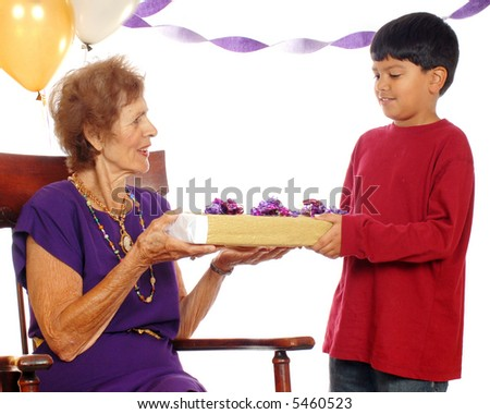 Senior woman at her birthday party, accepting a gift from her great grandson.