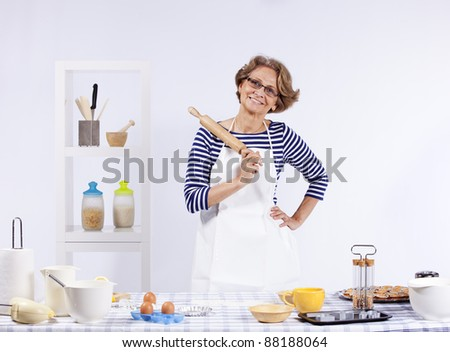 Senior woman at her kitchen showing you the rolling pin