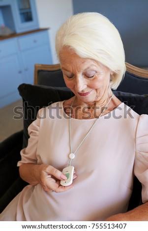 Senior Woman At Home Using Distress Alarm Call Button