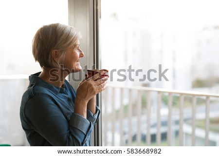 Senior woman at the window holding a cup of coffee #583668982