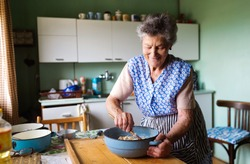 Senior woman baking pies in her home kitchen.  Mixing ingredients.