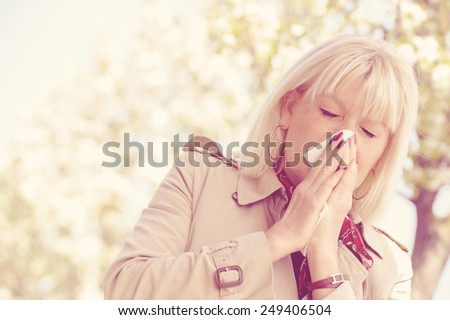 Senior woman blowing her nose outdoor