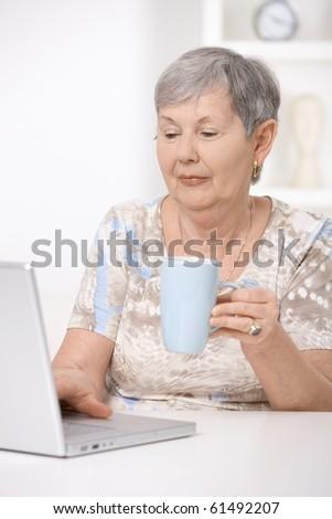 Senior woman browsing internet at home, using laptop computer.?