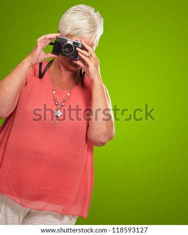 Senior Woman Clicking Photo Isolated On Green Background - stock photo