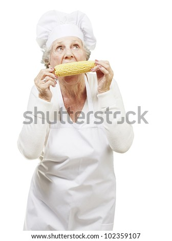 senior woman cook eating a corncob against a white background