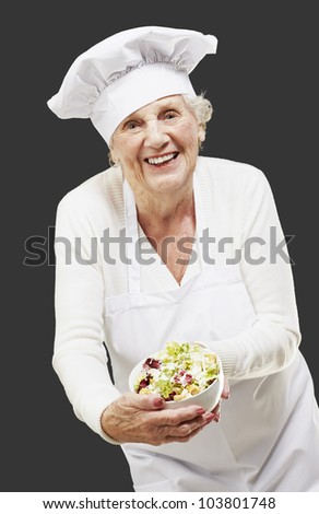 senior woman cook holding a bowl with salad against a black background