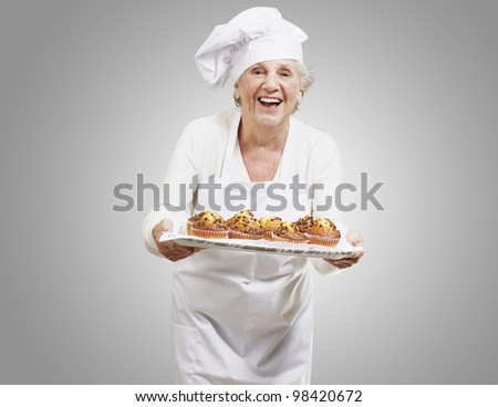 senior woman cook holding a tray with muffins against a grey background
