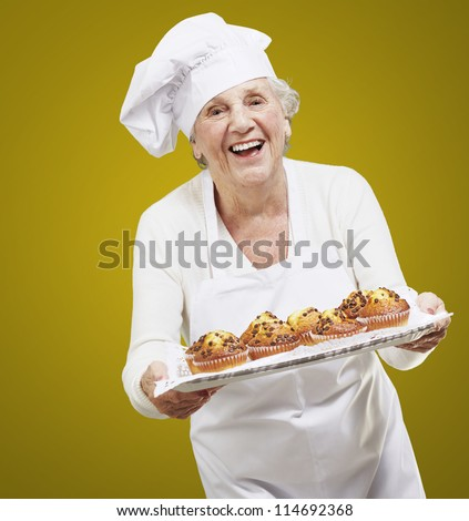 senior woman cook holding a tray with muffins against a yellow background - stock photo