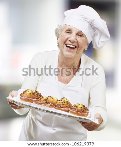 senior woman cook holding a tray with muffins, indoor