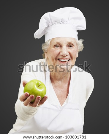 senior woman cook offering a green apple against a black background