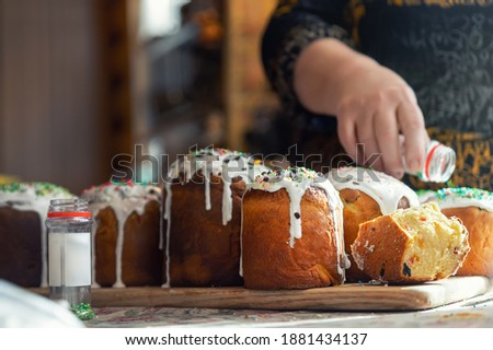 Senior woman cooking Traditional eastern europe Russian and ukrainian Easter cake kulich decorated with sweet sugar icing on wooden table morning sunlight ray. Tasty handmade orthodox paska bread Photo stock ©