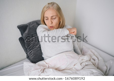 Senior woman coughing in arm sick of coronavirus viral infection spreading corona virus covering mouth and nose. Painful cough ill elderly patient lying in bed at home quarantine. First symptoms  Photo stock ©