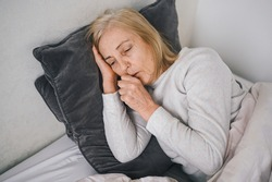 Senior woman coughing in fist sick of coronavirus viral infection spreading corona virus covering mouth and nose. Painful cough ill elderly patient lying in bed at home quarantine. First symptoms